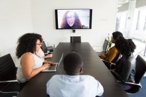 team meeting in conference room with one remote coworker calling in from the TV