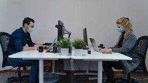 two coworkers wearing masks working in the office on their computers