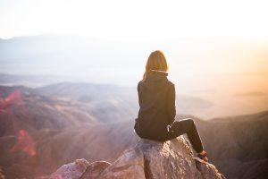 woman sitting on a rock in the mountains looking out to a viewpoint